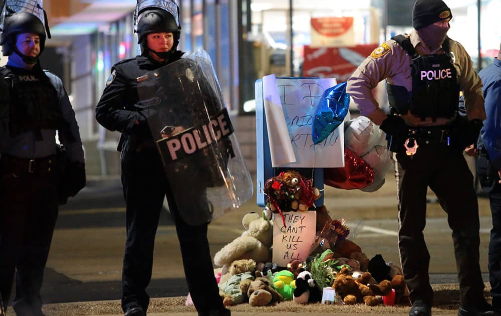 Police guard the entrance to a gas station in front of a memorial to Antonio Martin, in Berkeley, Mo. The mayor of the St. Louis suburb of Berkeley urged calm Wednesday after a white police officer killed black 18-year-old Antonio Martin who police said pointed a gun at him, reigniting tensions that have lingered since the death of Michael Brown in neighboring Ferguson.