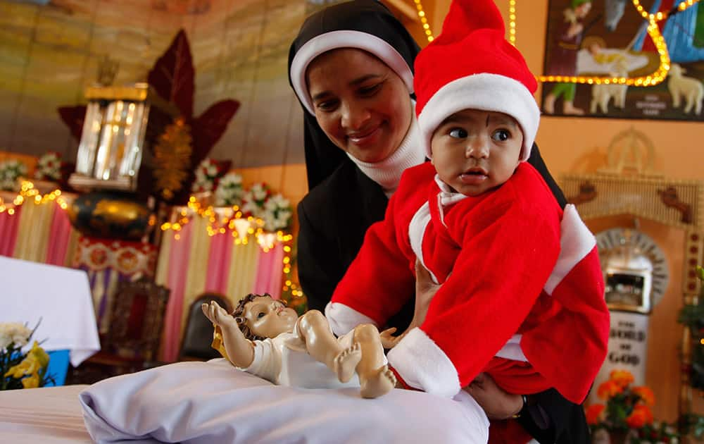 A nun shows a child in a Santa suit a statue of baby Jesus after Christmas prayers at St. Mary's Garrison church, in Jammu.