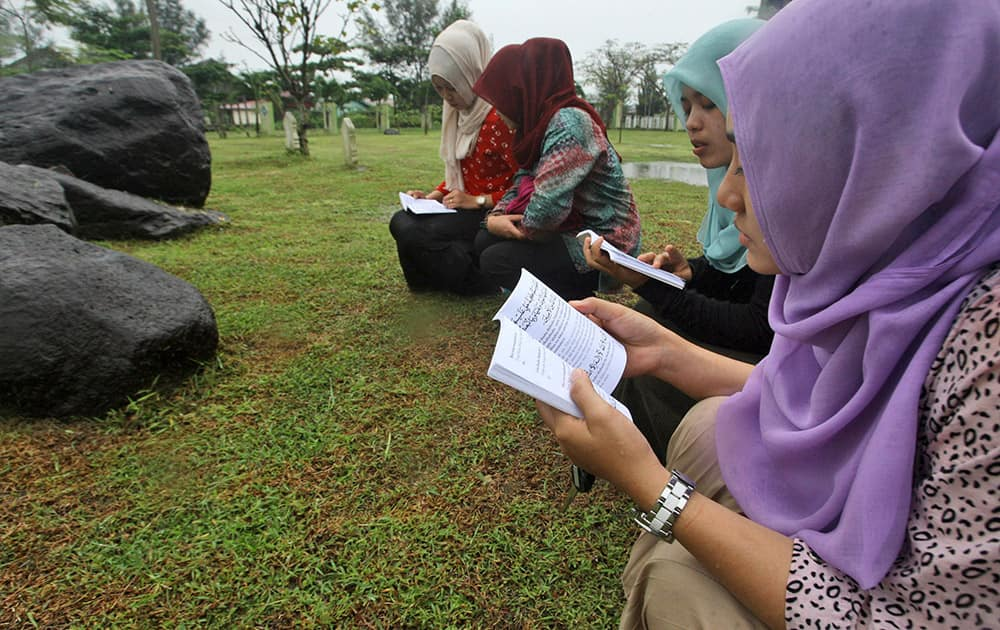 Acehnese women pray for the victims of 2004 Indian Ocean tsunami at a mass grave in Banda Aceh, Aceh province, Indonesia. Aceh, the worst-hit region by Indian Ocean tsunami, is preparing to commemorate the 10th anniversary of the Boxing Day tsunami that killed more than 100,000 people in the province.