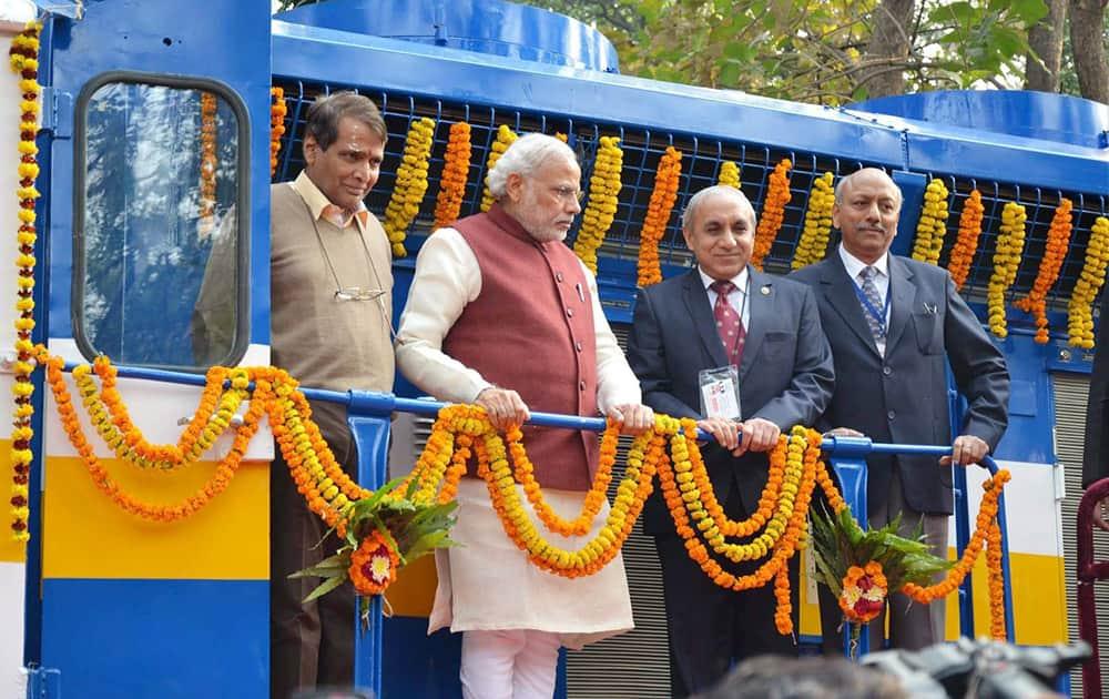 Prime Minister Narendra Modi with Union Minister for Railways Suresh Prabhakar Prabhu and Chairman of Railway Board Arunendra Kumar on the new high horsepower diesel locomotive, at Diesel Locomotive Works (DLW), in Varanasi.