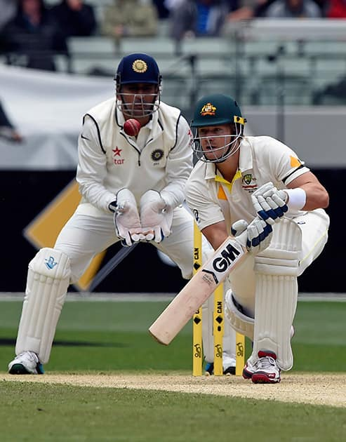MS Dhoni, watches on as Australia's Shane Watson bats during their play on day one of the third cricket test in Melbourne, Australia.