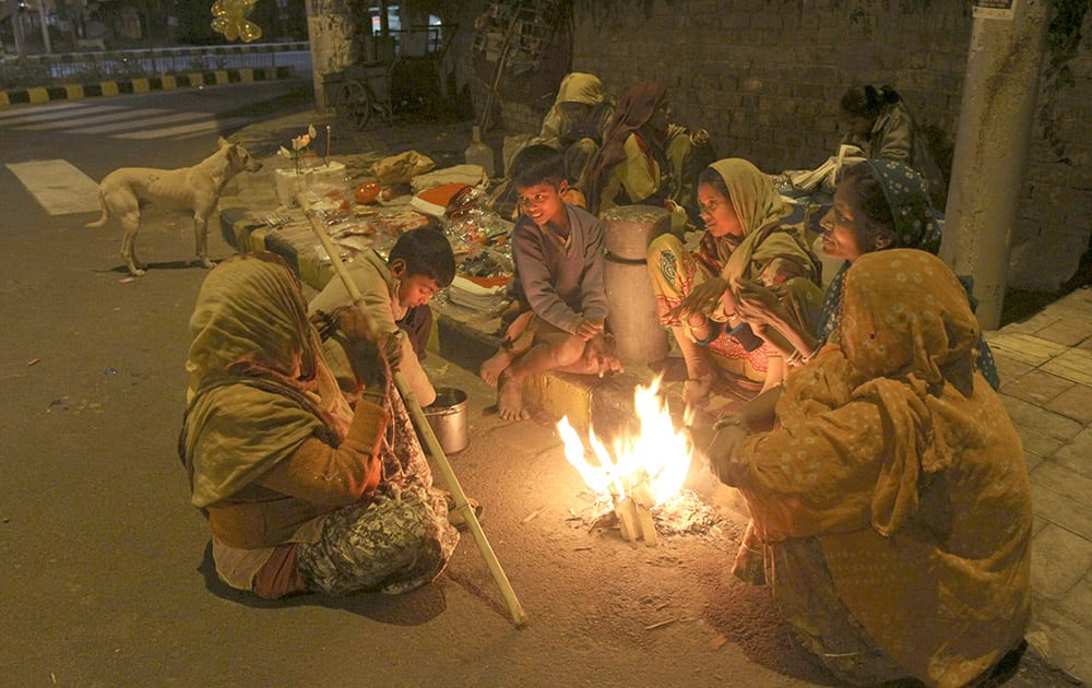 Family living on a roadside keeps themselves warm by sitting around a bonfire in Ahmedabad.