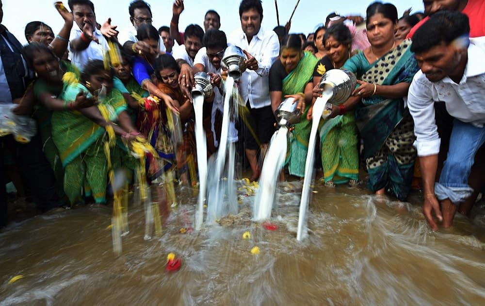 Fishermen pour milk into the sea to mark the 10th anniversary of Tsunami at Marina beach.