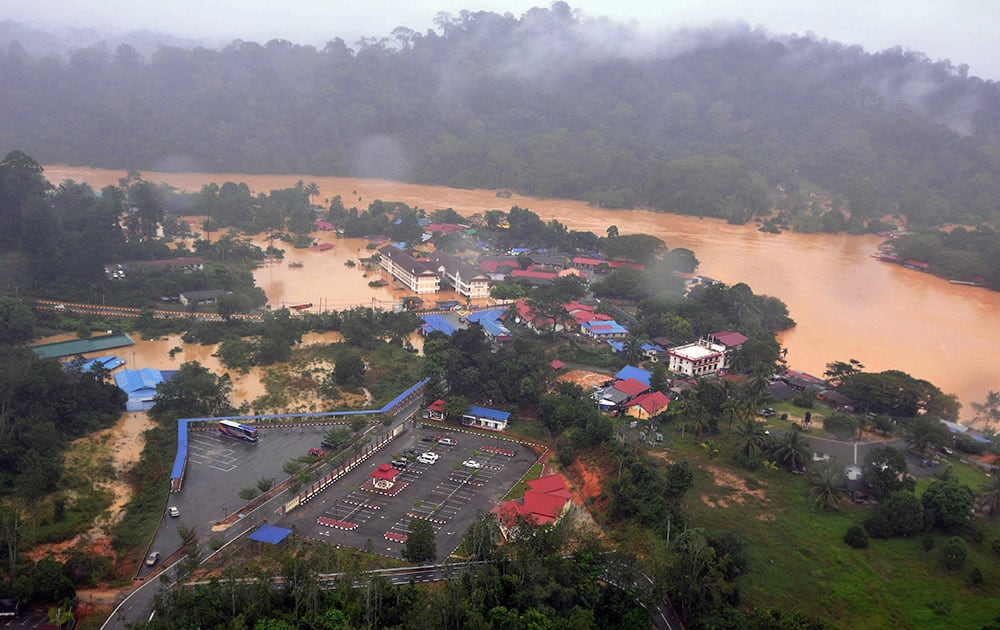 Numbers of houses and buildings along a flooded river stand in muddy water in Malaysia National Park in Kuala Tahan, Pahang state, Malaysia.