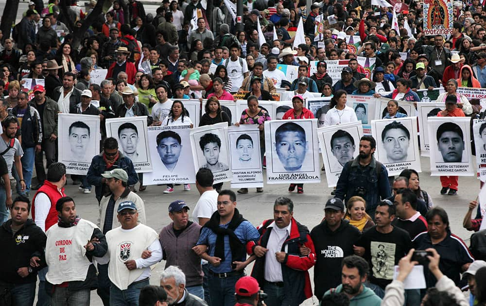 Relatives of the 43 missing students from the Isidro Burgos rural teachers college march holding pictures of their missing loved ones during a protest in Mexico City.