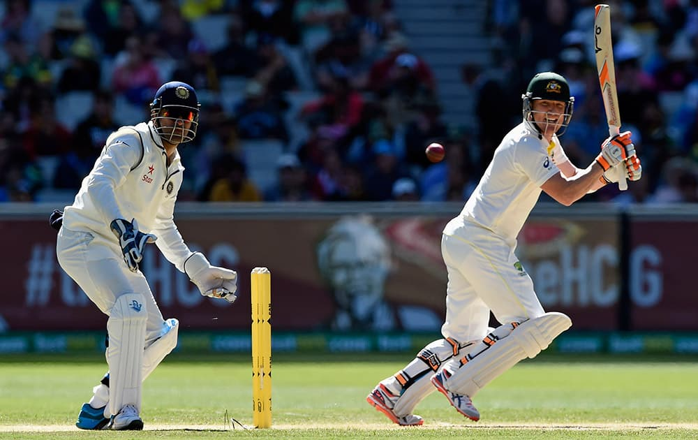 Australia's Brad Haddin, hits a cut shot as India's MS Dhoni, watches on during their play on day one of the third cricket test in Melbourne, Australia.