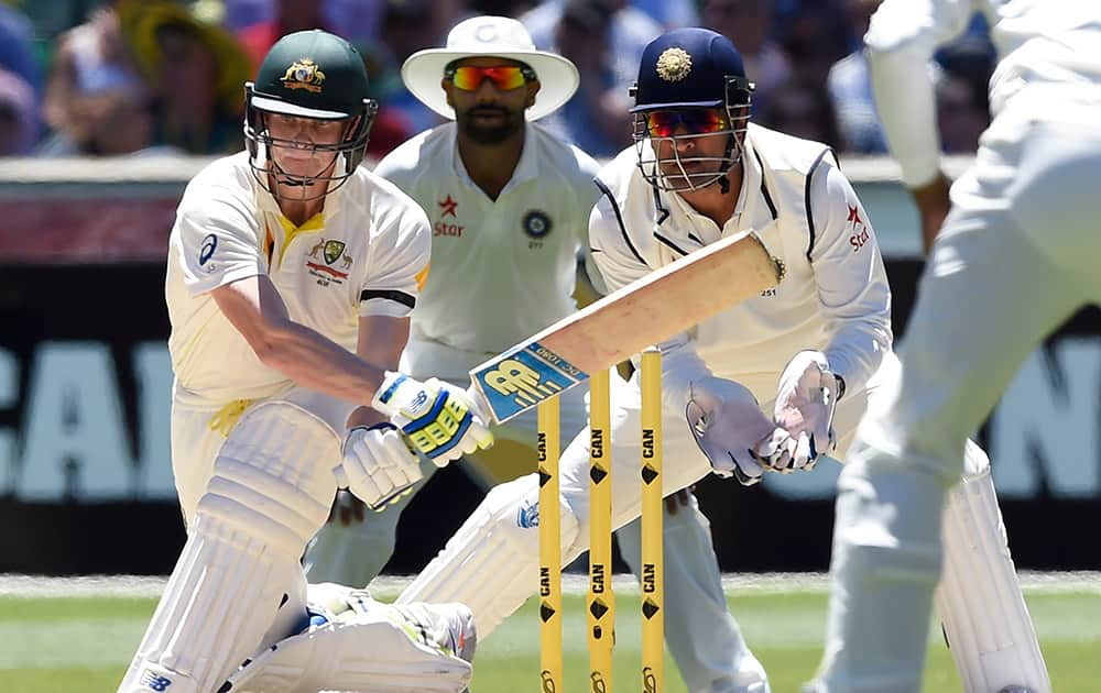 Australia's Steve Smith, attempts to sweep the ball in front of wicketkeeper MS Dhoni, on the second day of their cricket test match in Melbourne, Australia.