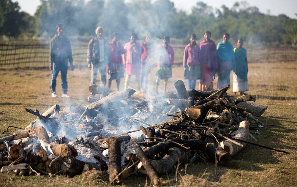 Tribal people watch mass cremation of villagers who were killed during an attack by an indigenous separatist group, in a field near a relief camp at Tinsuti village in Sonitpur district of Indian eastern state of Assam.
