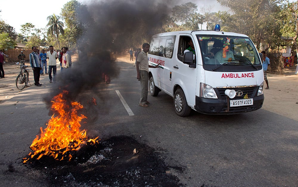 Tribal people allow an ambulance to go as they burn tires to block a national highway during a twelve hour general strike in Biswanath Chariali in Indian northeastern state of Assam.