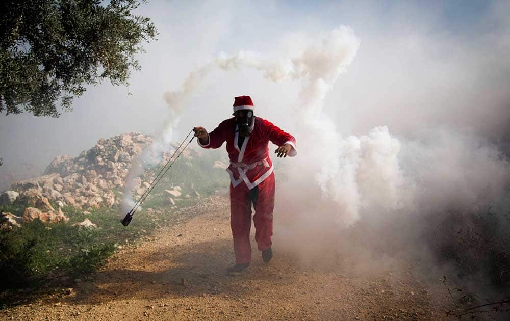 A Palestinian protester wearing a Santa Claus costume uses a sling to throw back a tear gas canister fired by Israeli soldiers during a protest against Israel's separation barrier outside the West Bank village of Bilin, near Ramallah.