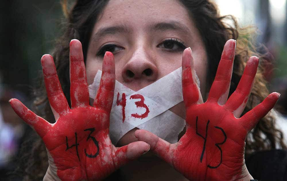 A woman holds up her red-painted hands and the number 43 written on them to remember the 43 missing students from the Isidro Burgos rural teachers college during a protest in Mexico City.