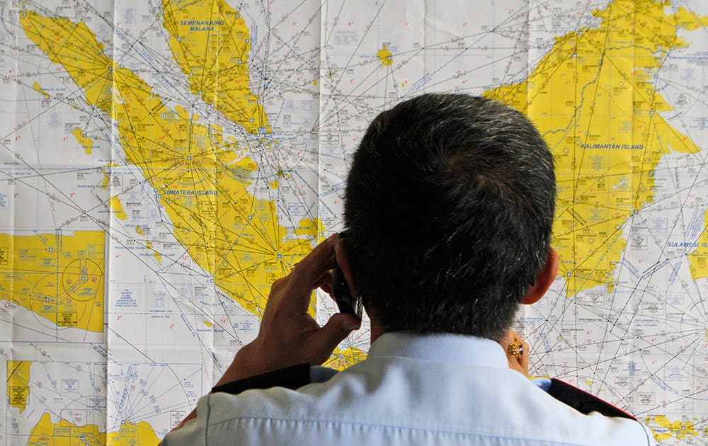 An airport official checks a map of Indonesia at the crisis center set up by local authority for the missing AirAsia flight QZ8501, at Juanda International Airport in Surabaya, East Java, Indonesia.