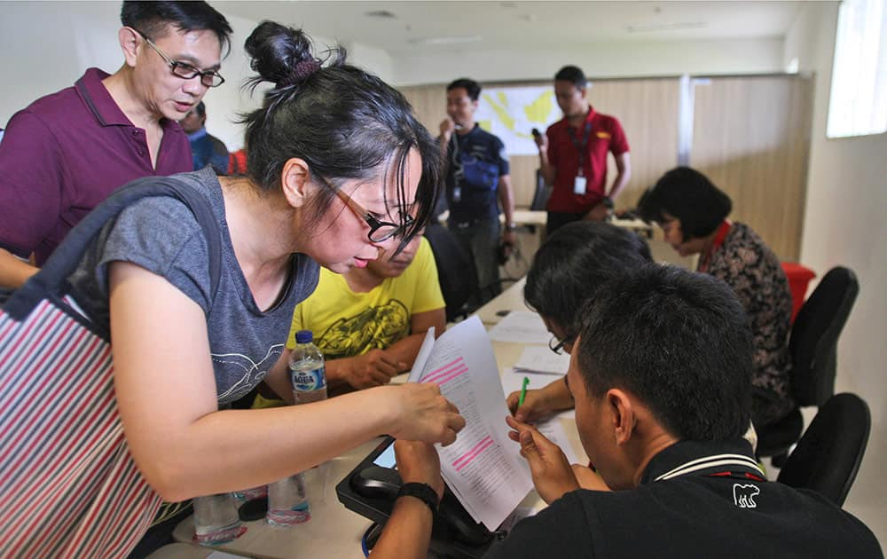 Relatives of the passengers onboard AirAsia flight QZ8501 check the plane's manifest at a crisis center set up by local authority at Juanda International Airport in Surabaya, East Java, Indonesia.