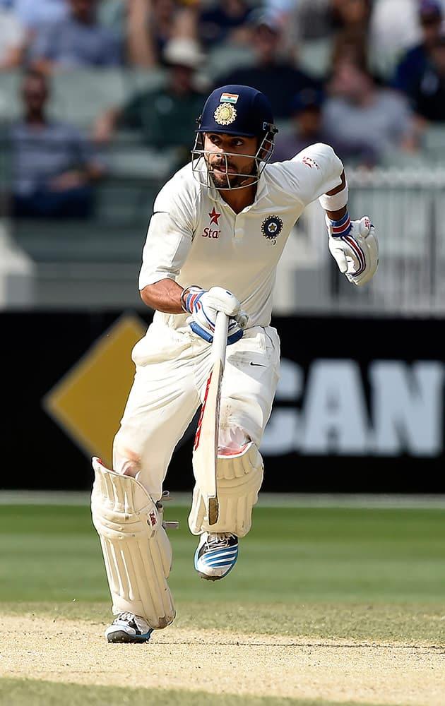 India's Virat Kohli runs between the stumps on the third day of their cricket test match against Australia Melbourne, Australia, Sunday.
