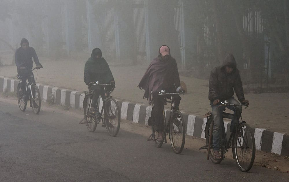 Mens pedal their bicycles at a road during a foggy morning in New Delhi.