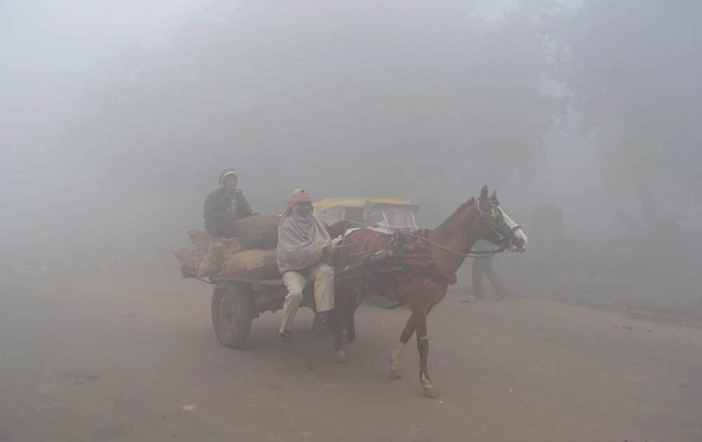 People on their way during a foggy morning in Mathura.