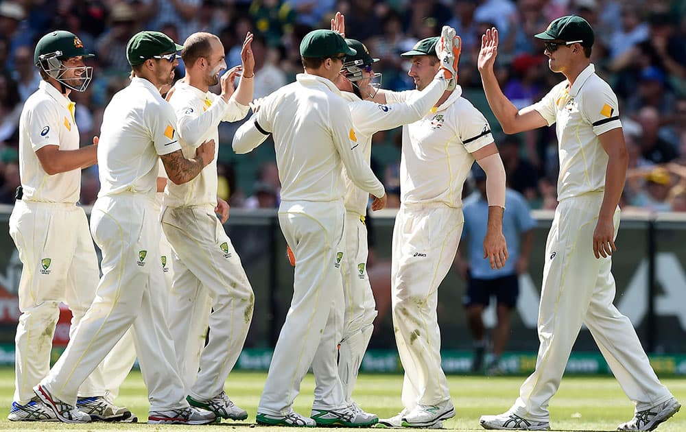 Australian teammates celebrate the wicket of India's Lokesh Rahul for 3 runs on the third day of their cricket test match in Melbourne, Australia.