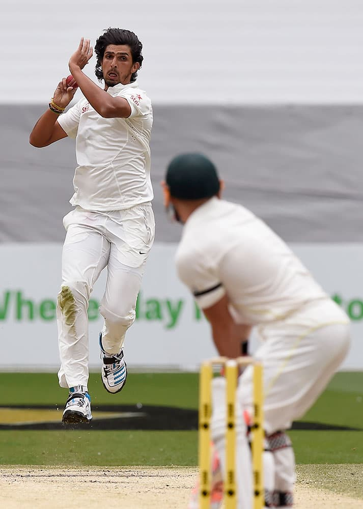India's Ishant Sharma bowls to Australia's David Warner, right, on the fourth day of their cricket test match in Melbourne, Australia.