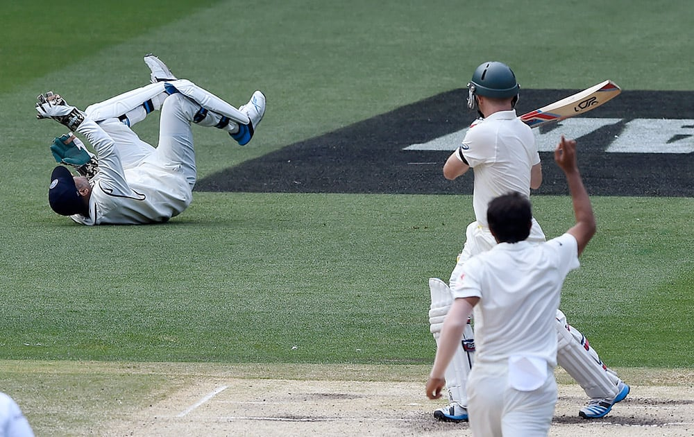 Australia's Chris Rogers, watches his shot fall short of India's MS Dhoni, off the bowling of Mohammed Shami, on the fourth day of their cricket test match in Melbourne, Australia.