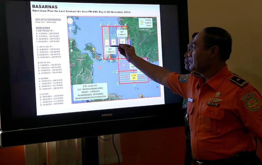 A member of Indonesian National Search and Rescue Agency (BASARNAS) shows a map of searching area on screen during a briefing prior to a search and rescue operation of the missing AirAsia flight QZ8501, at Pangkal Pinang command post, Sumatra Island, Indonesia.