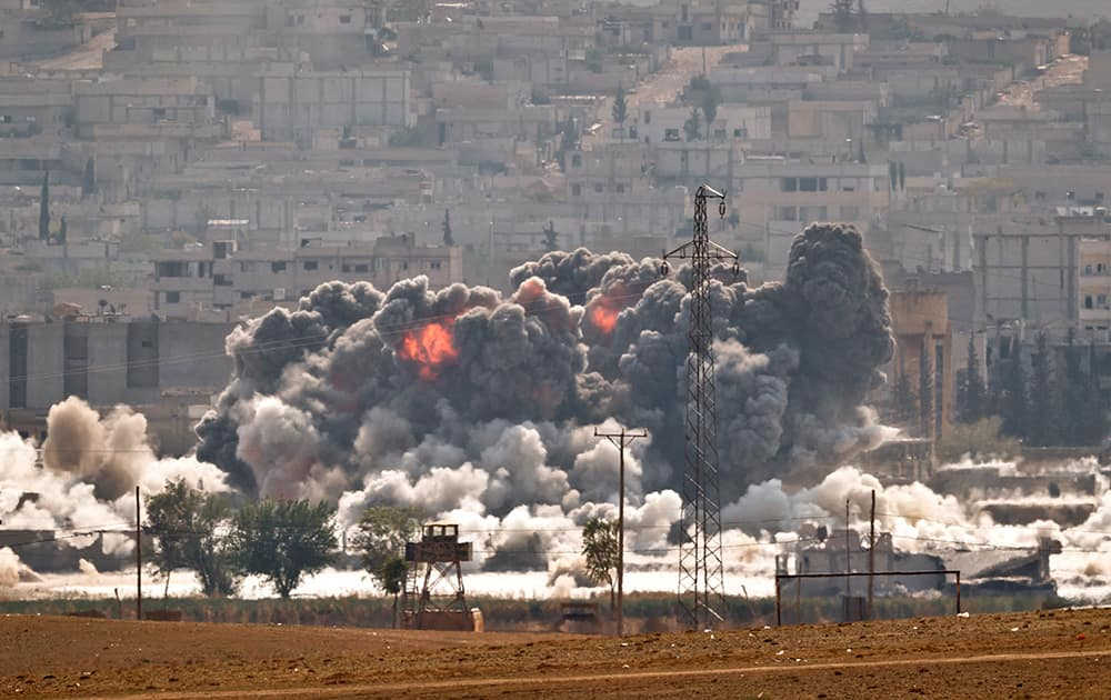 SMOKE AND FLAMES RISE FROM AN ISLAMIC STATE FIGHTERS' POSITION IN THE TOWN OF KOBANI DURING AIRSTRIKES BY THE US LED COALITION SEEN FROM THE OUTSKIRTS OF SURUC, NEAR THE TURKEY-SYRIA BORDER. KOBANI, ALSO KNOWN AS AYN ARAB, AND ITS SURROUNDING AREAS, HAS BEEN UNDER ASSAULT BY EXTREMISTS OF THE ISLAMIC STATE GROUP SINCE MID-SEPTEMBER AND IS BEING DEFENDED BY KURDISH FIGHTERS.
