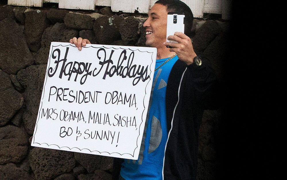 A man holds a sign wishing the first family