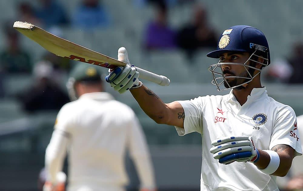 India's Virat Kohli raises his bat after making 50 runs against Australia on the final day of their cricket test match in Melbourne, Australia.