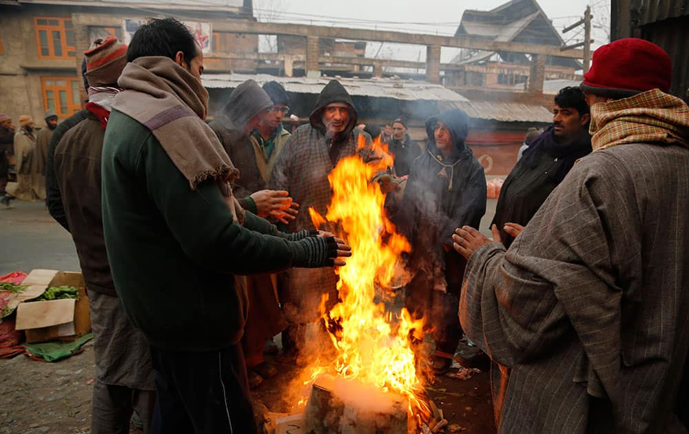Kashmiri men warm their hands standing near a bonfire on a cold and foggy morning in Srinagar.