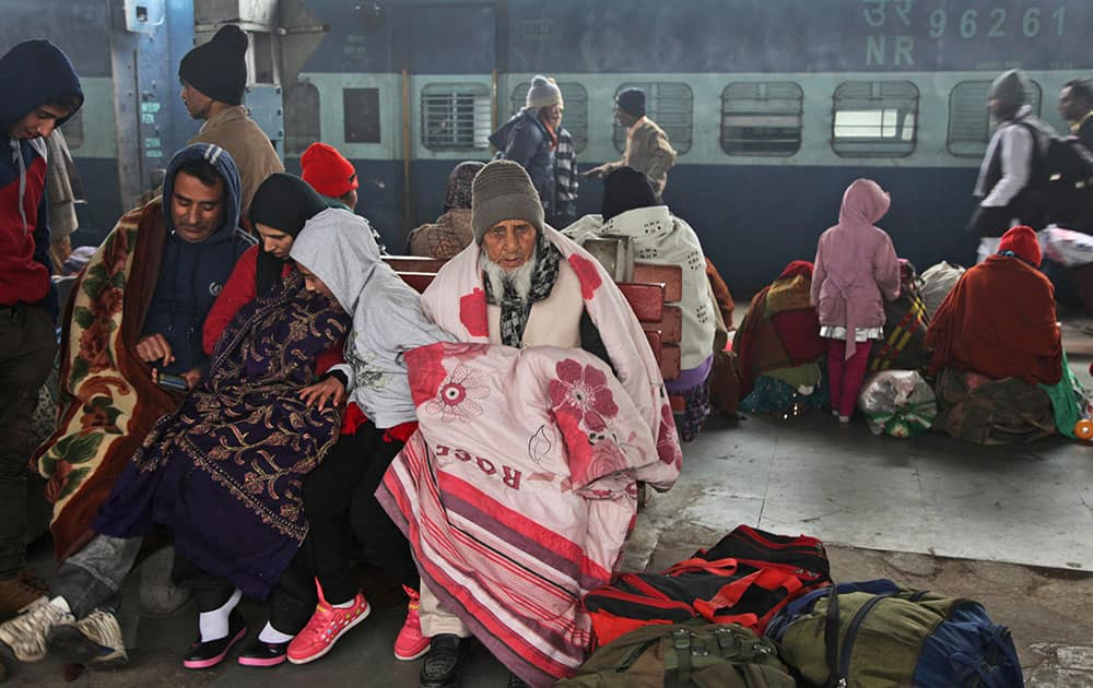 Passengers wait for a train amidst morning fog in Jammu. Cold wave conditions continue unabated in the northern region with fog enveloping most areas and affecting transport services.