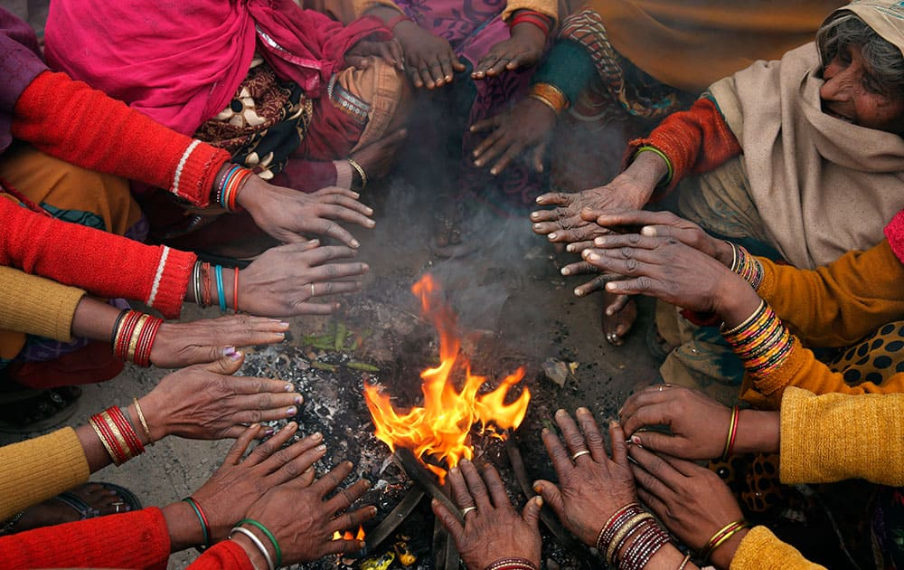 Passengers warm themselves around a fire as they wait for their train to arrive on a cold morning, in Allahabad.