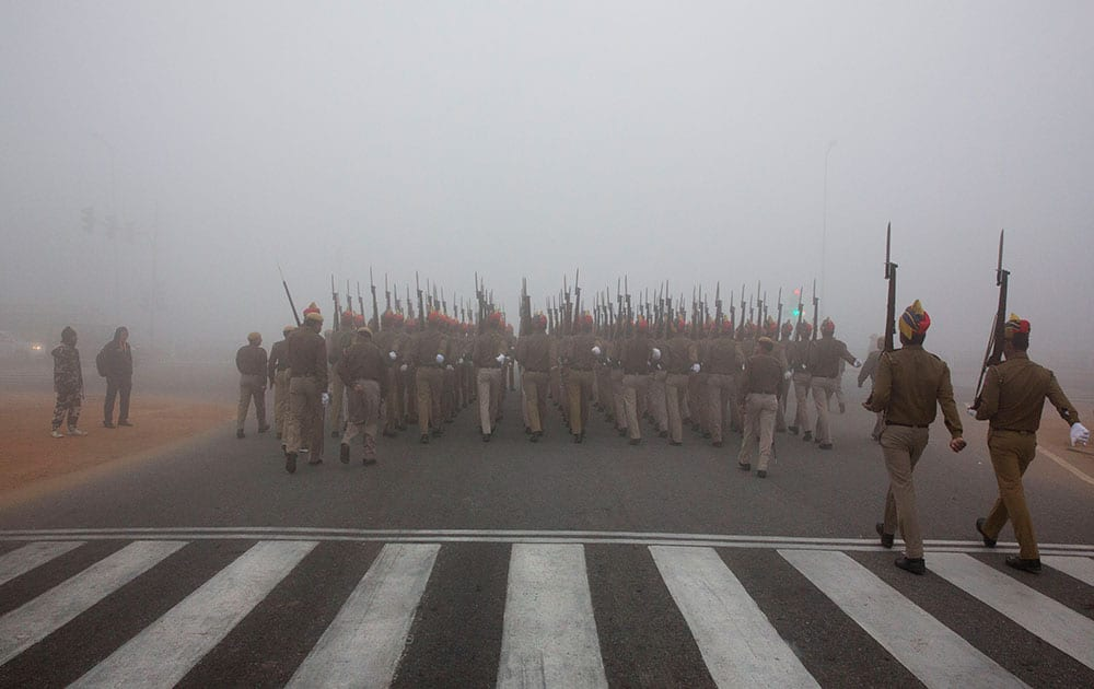 Delhi police personnel practice marching in preparation for the upcoming Republic Day parade amidst morning fog in New Delhi.