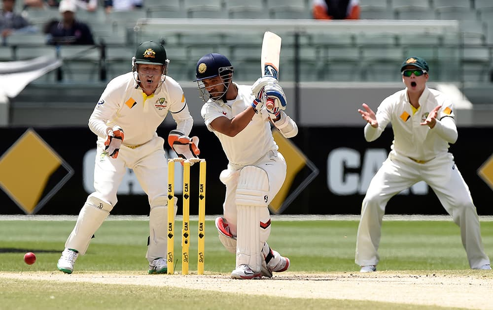 Ajinkya Rahane, drives the ball in front of Australia's Brad Haddin and Steve Smith on the final day of their cricket test match in Melbourne, Australia.