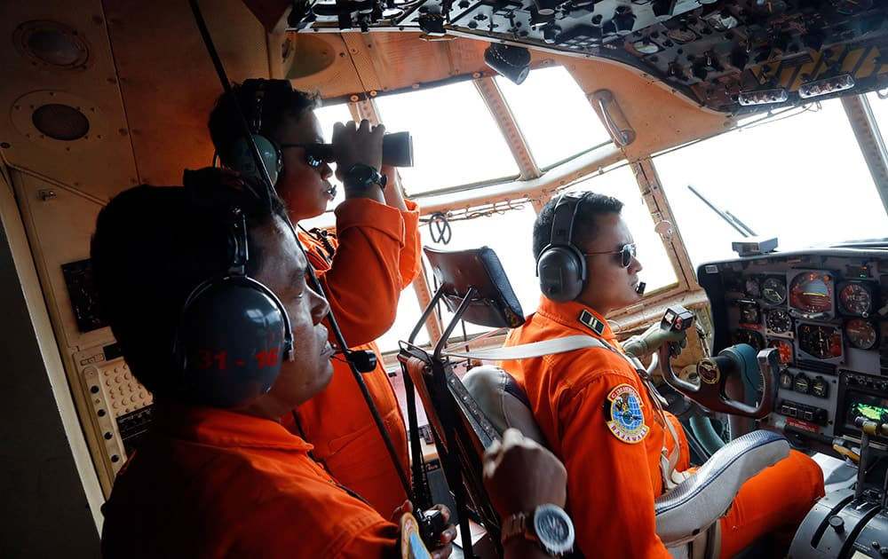 Crew of Indonesian Air Force C-130 airplane of the 31st Air Squadron scan the horizon during a search operation for the missing AirAsia flight 8501 jetliner over the waters of Karimata Strait in Indonesia.