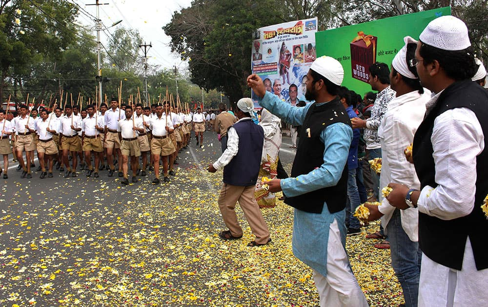 Muslims shower flower petals as volunteers of Hindu nationalist group Rashtriya Swayamsevak Sangh, (RSS), parent organization of the Bharatiya Janata Party (BJP), march on the concluding day of their three-day meeting in Bhopal, India.