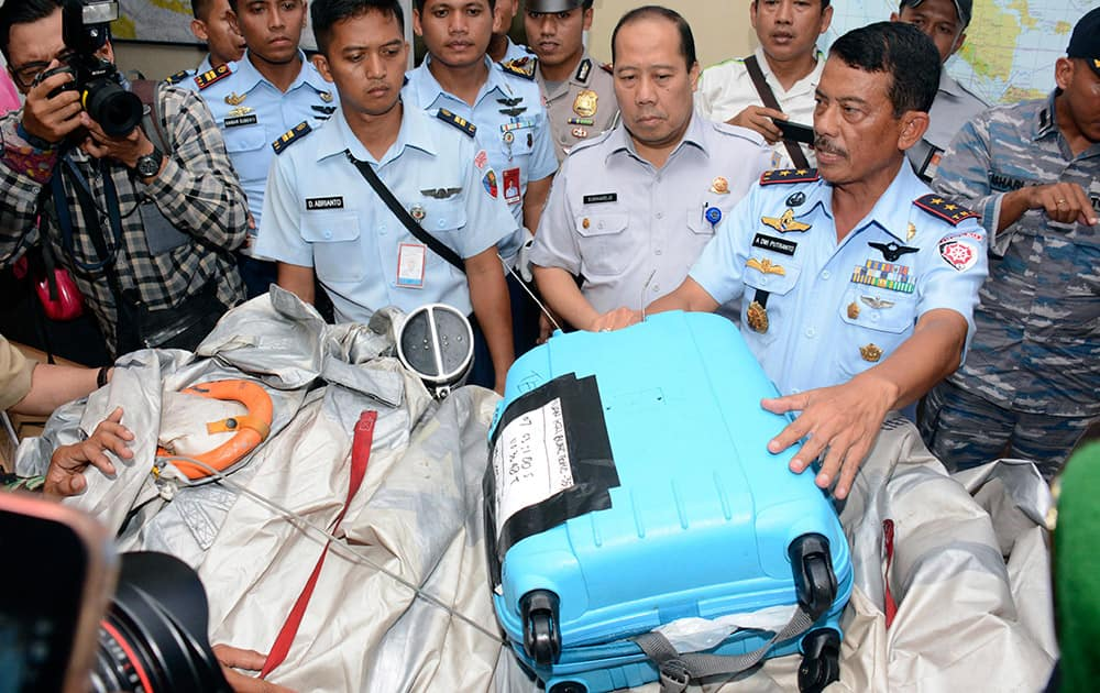 Commander of 1st Indonesian Air Force Operational Command Rear Marshall Dwi Putranto, right, shows airplane parts and a suitcase found floating on the water near the site where AirAsia Flight 8501 disappeared, during a press conference at the airbase in Pangkalan Bun, Central Borneo, Indonesia.