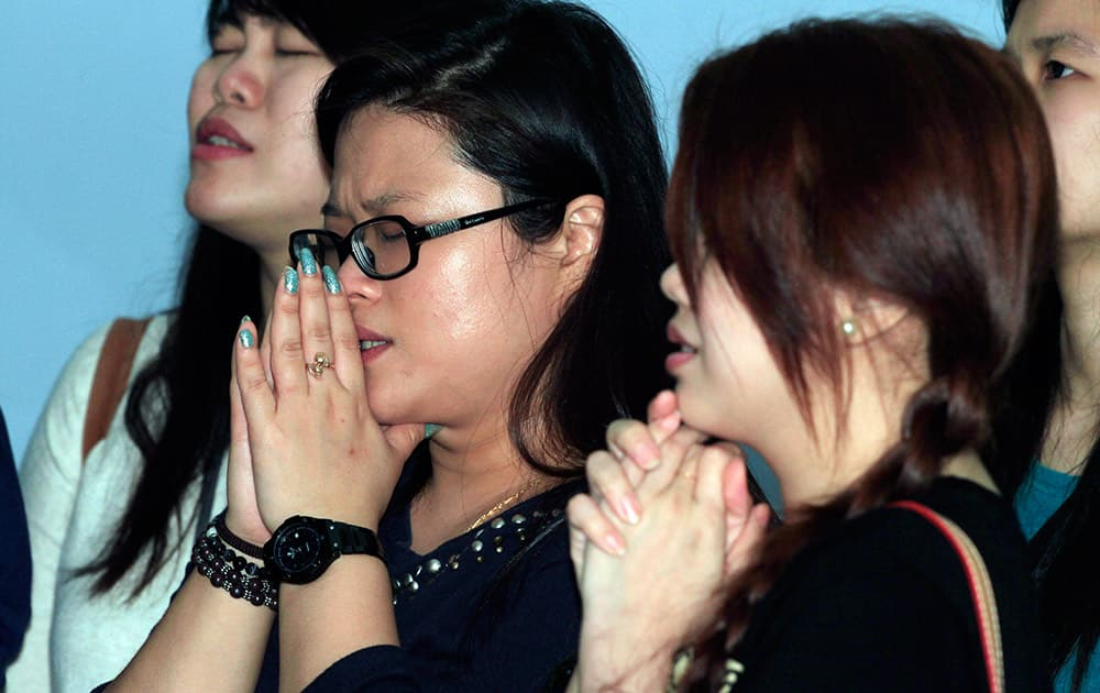 Relatives of passengers of AirAsia Flight 8501 pray at Juanda International Airport in Surabaya, East Java, Indonesia.