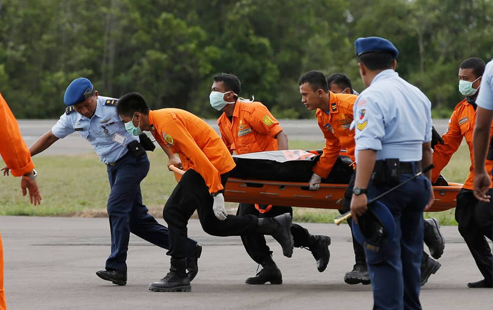 Officers of the National Search And Rescue Agency (BASARNAS) carry a body of one of the victims on board the ill-fated AirAsia Flight 8501, from a helicopter upon arrival at the airport in Pangkalan Bun, Indonesia.