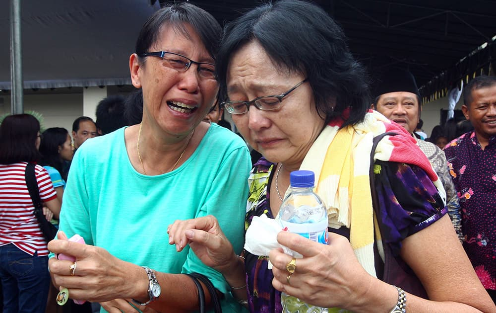 Relatives of passengers of AirAsia Flight 8501 cry after visiting the crisis center at Juanda International Airport in Surabaya, East Java, Indonesia.