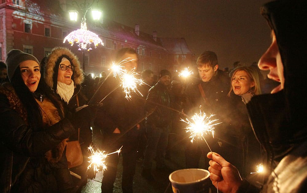 People gather to see fireworks display and celebrate the New Year at Castle Square in Warsaw, Poland.