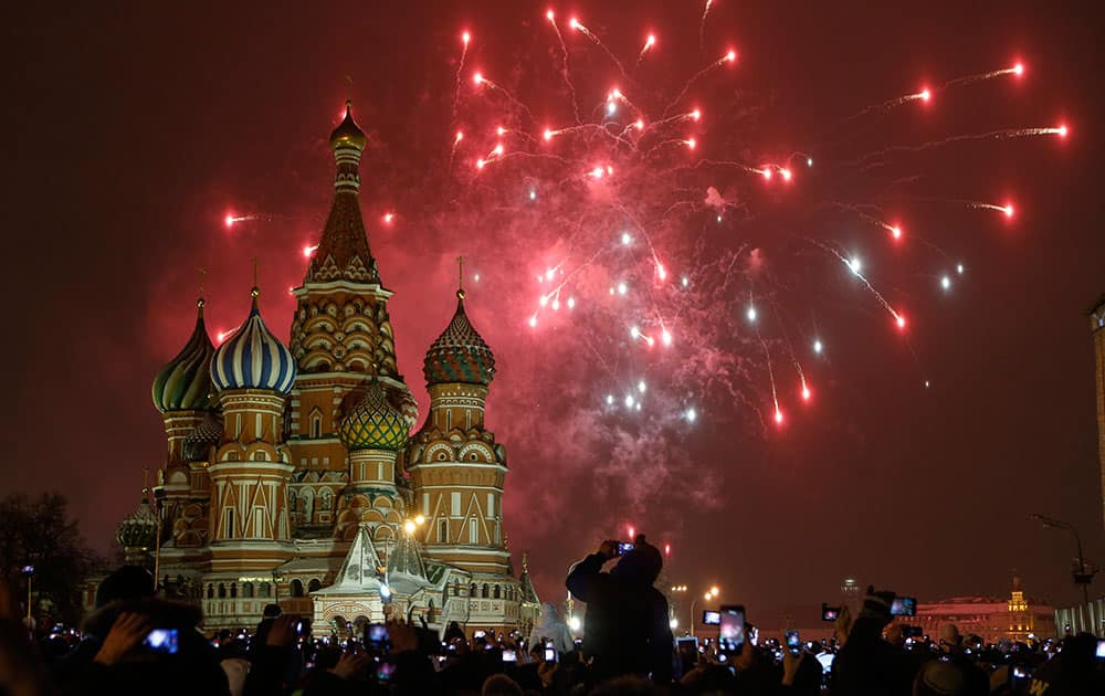 People photograph fireworks as they celebrate the New Year in Red Square in Moscow, Russia.