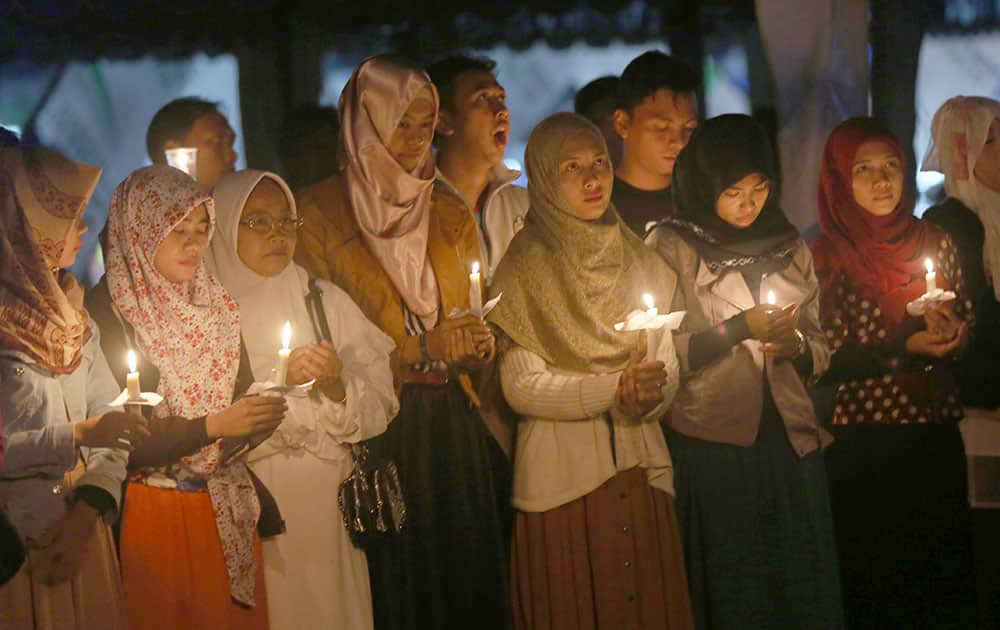 Indonesians hold candles to pray for the victims of AirAsia Flight 8501 in Pangkalan Bun, Indonesia.