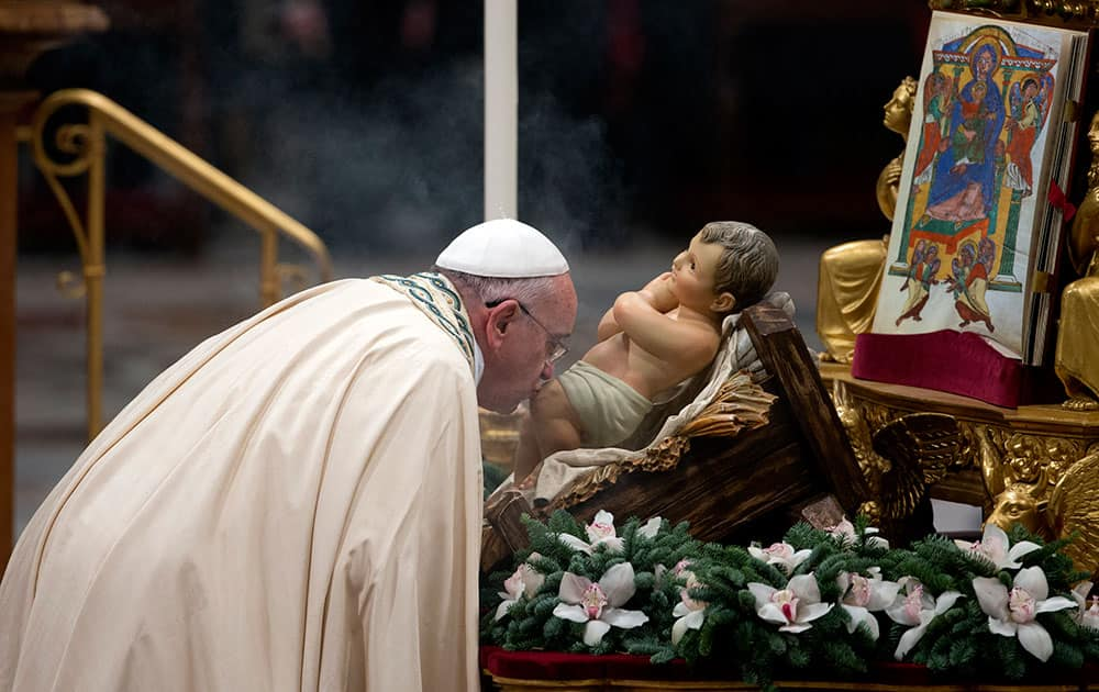 Pope Francis kisses a statue of the baby Jesus as he arrives to celebrate the new year's eve vespers Mass in St. Peter's Basilica at the Vatican.
