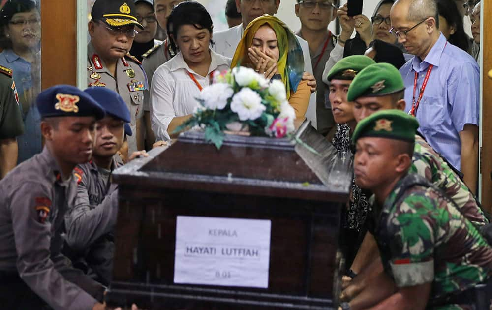 A relative, weeps as Indonesian soldiers lift a coffin containing the body of Hayati Lutfiah, one of the victims of AirAsia Flight 8501, during the handover ceremony to her family at the police hospital in Surabaya, East Java, Indonesia.