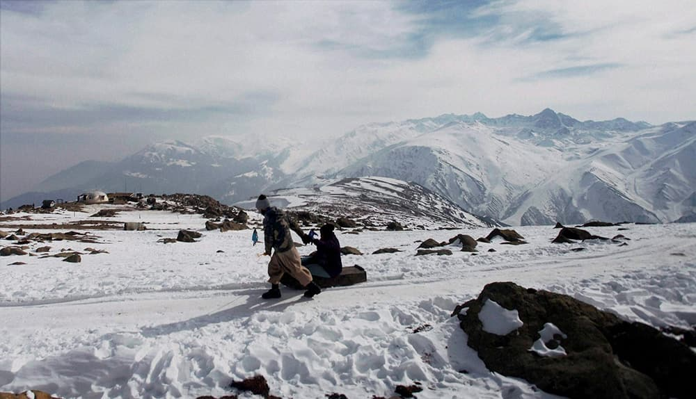 A tourist enjoys a sledge ride on the snow-covered, new years day in Gulmarg.