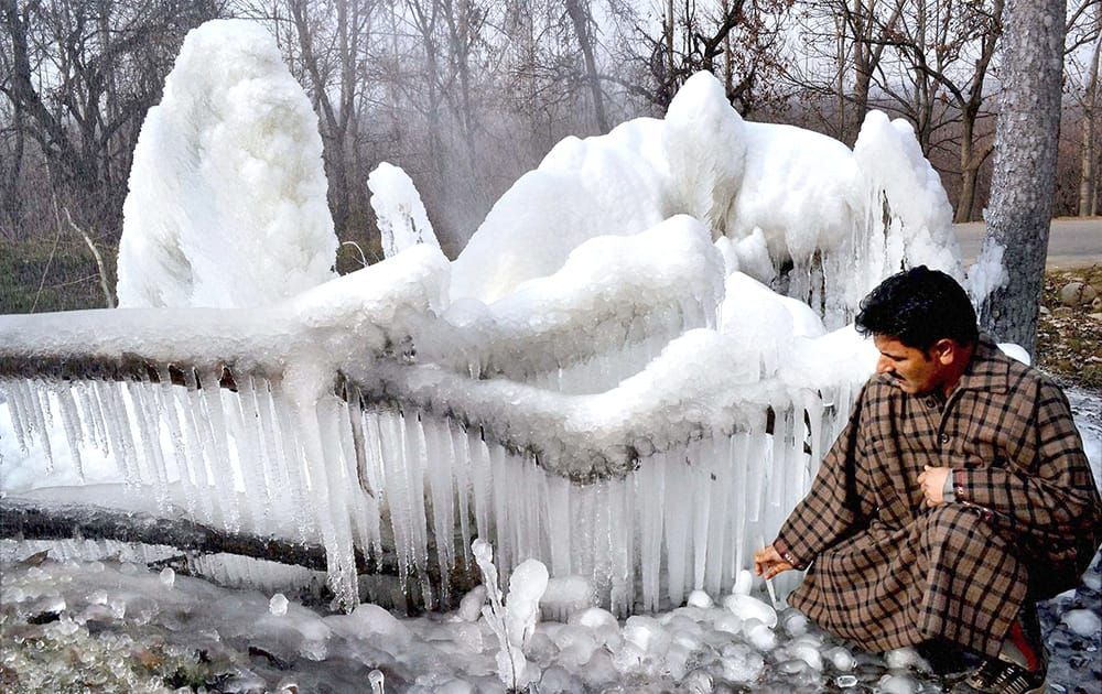 A man breaks icicles formed in a stream and in trees due to sub zero tempatures in the valley, in Srinagar.
