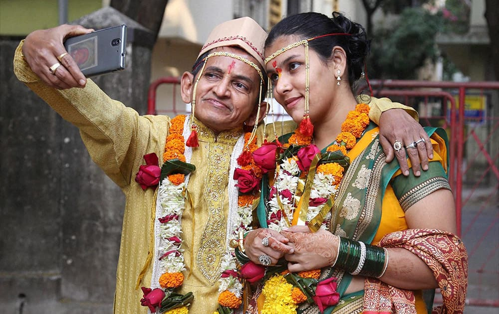 Satish Apte, 58, takes a selfie with his 20-year-old wife, Lisa, in Thane.