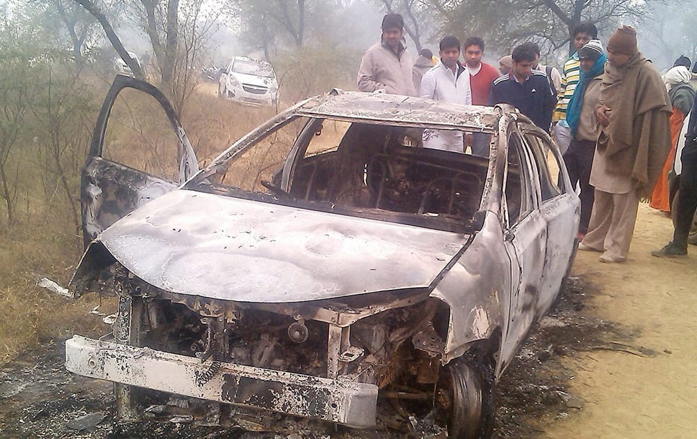 People look on damaged car in which four Delhi youth found charred inside the car at a village in Jhajjar district of Haryana.