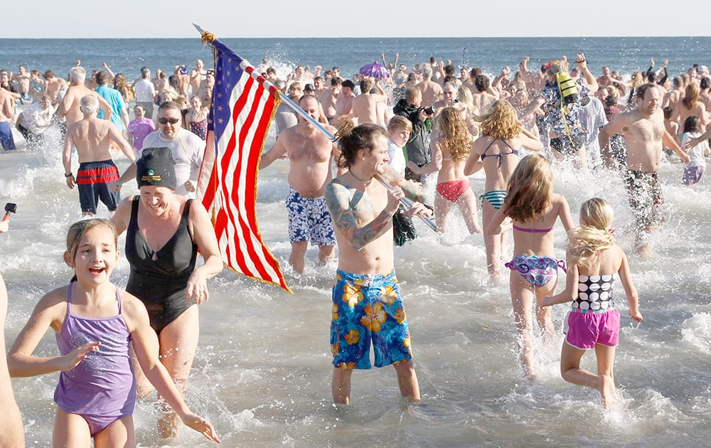 People run in and out of the cold Atlantic Ocean during the Sons of Ireland's annual New Year's Day Polar Bear Plunge on a sunny, but frigid, in Asbury Park, N.J.