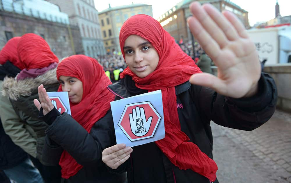 Two young girls carrying leaflets saying 'don't touch my mosque' participate in a demonstration at the parliament in Stockholm. Three mosques have suffered arson attacks in Sweden since Christmas Day.