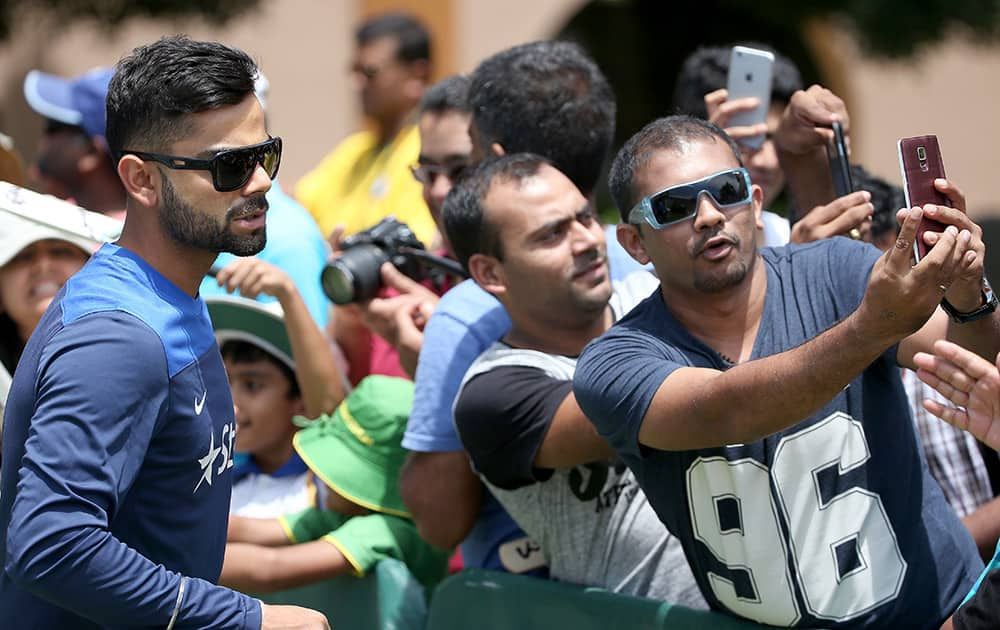 India's cricket captain Virat Kohli, left, poses for photos for fans as his team arrives at training before their cricket test match against Australia in Sydney, Sunday.